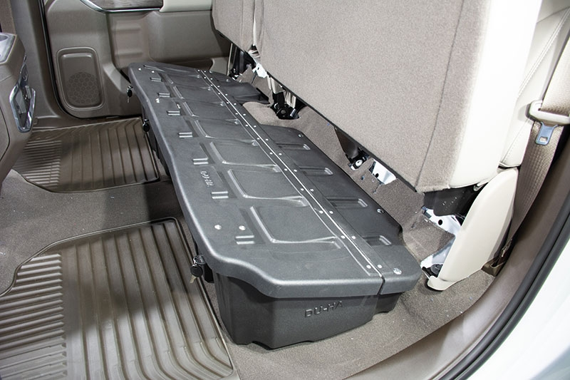 The DU-HA fits underneath the pre-existing back seats of your truck. The DU-HA will hold larger items without the organizers / gun rack installed.